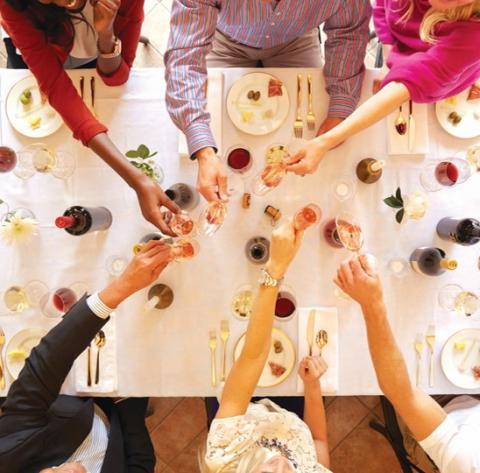 Overhead view of people toasting across a table set with wine.